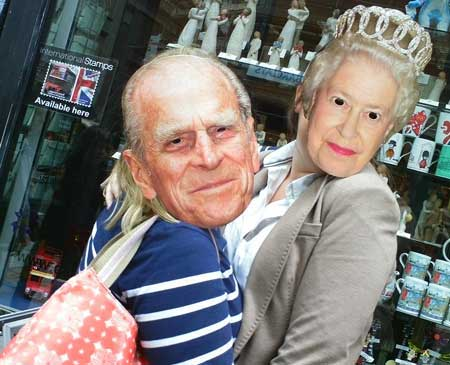 Two people wearing The Queen and Prince Philip masks on the streets of London.