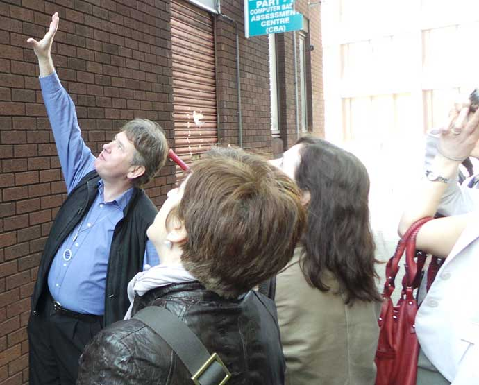 London tour guide Richard Jones pointing at the Little Dorrit pages that are on a wall in Southwark.