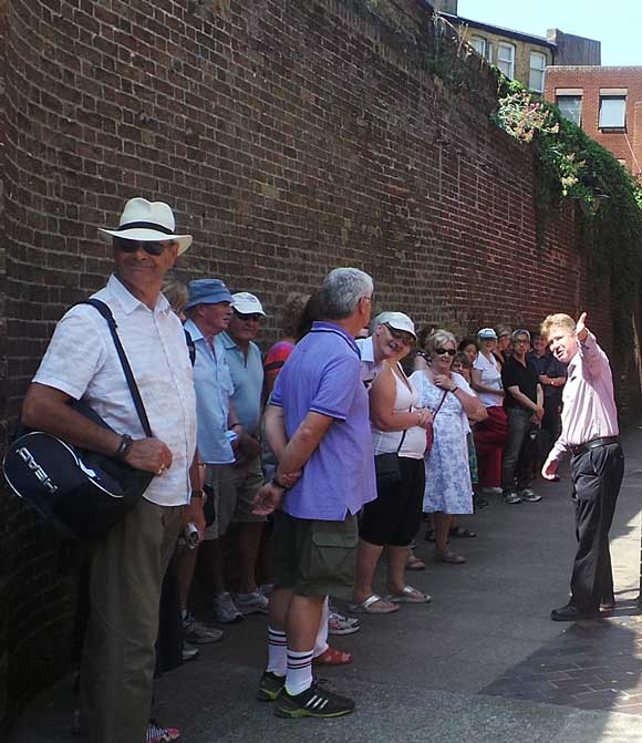 Richard guiding a Dickens tour and standing alongside the wall of the Marshalsea Prison.